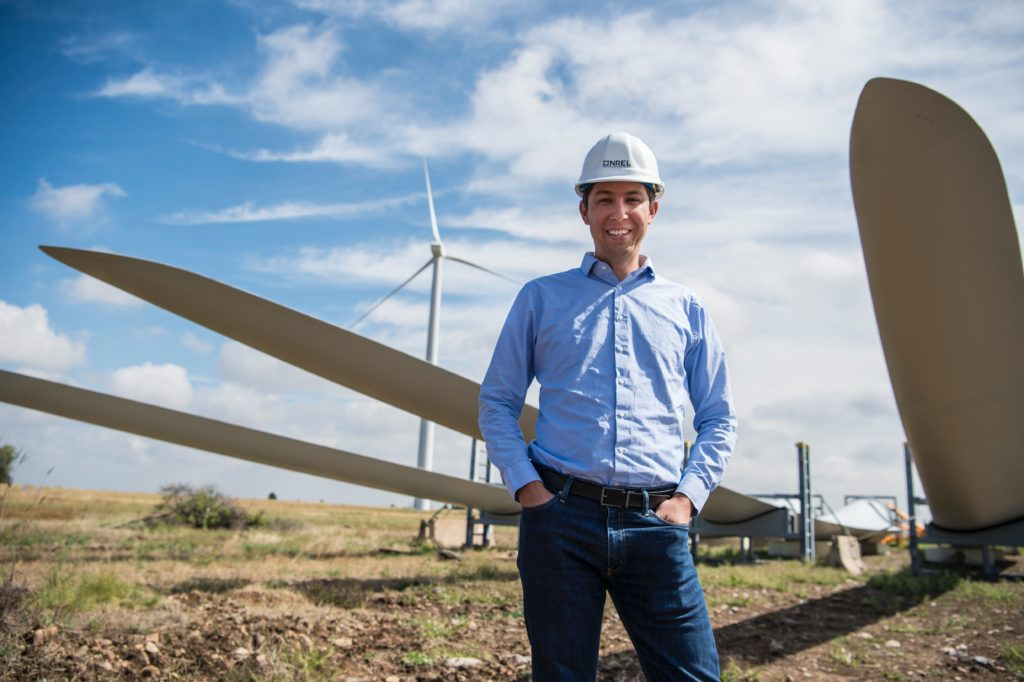 man smiling and standing near windmill